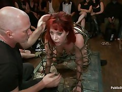 They've putted her in a special cage and as the bald man fucks her sexy mouth, 3 dirty strumpets are taking worthy care of her ass. That babe is fucked from both ends and the sex toy and fingering she's getting on her arse only makes her mouth want to swallow that dick as deep as she can while the public see her.