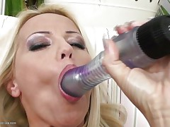 Blond milf wearing only a pair of hot dark stockings is playing solo with her large dildo, that babe sucks it and the fills her shaved vagina with it, fucking herself as hard as that babe can but that is not enough. Luckily her brunette girlfriend is ready to assist and gives her a hand, rubbing her muff and then fingering it, want to watch what else she's ready to do?